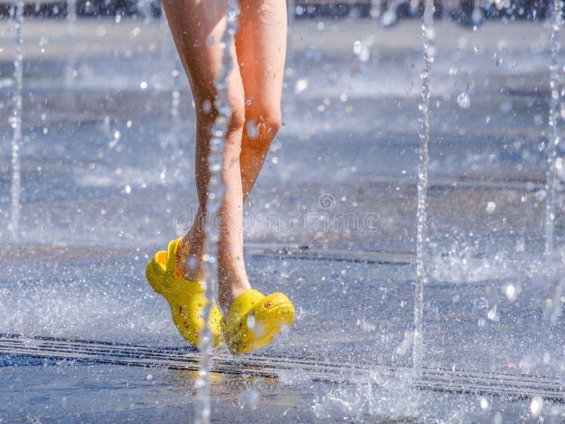 Le gambe di un bambino in scarpe di gomma gialle che passa il rinfresco spruzza della fontana della città un giorno di estate cal fotografie stock