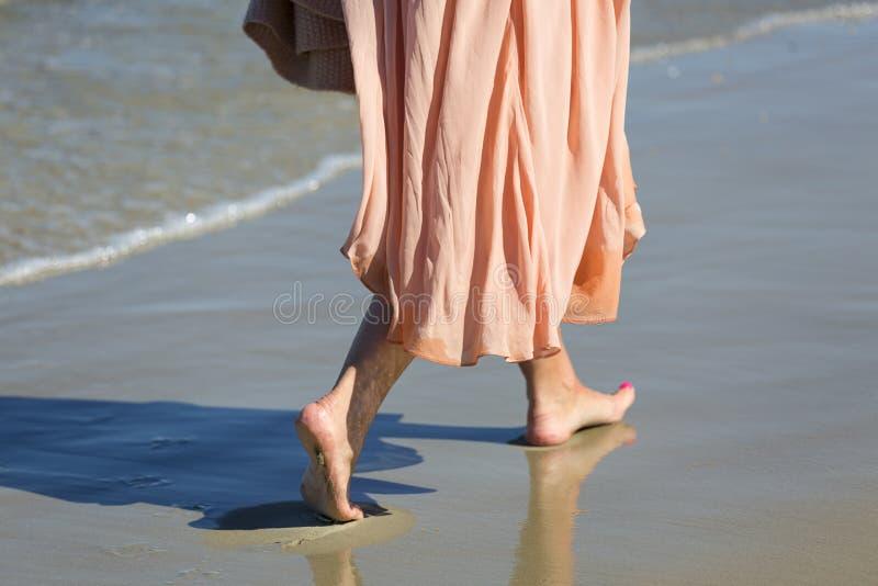 Le gambe di una donna in vestito rosa che cammina a piedi nudi sulla sabbia bagnata, Sopot, Polonia fotografia stock