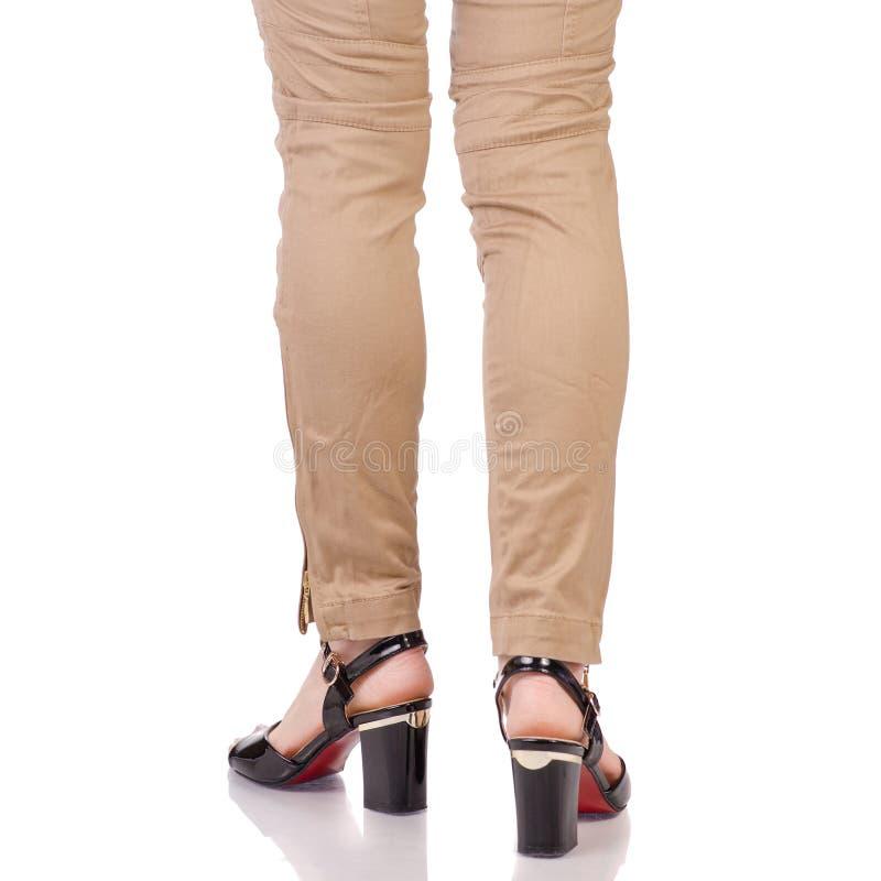 Le gambe femminili in classico ansima lo stile nero del classico delle scarpe della lacca fotografia stock