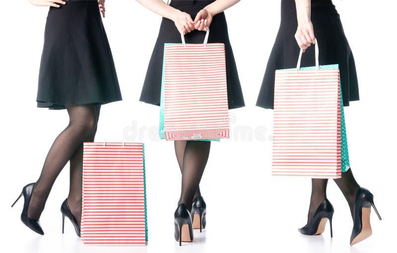 Le gambe femminili messe nelle borse nere delle scarpe dei tacchi alti imballano il modo nero della gonna immagine stock libera da diritti