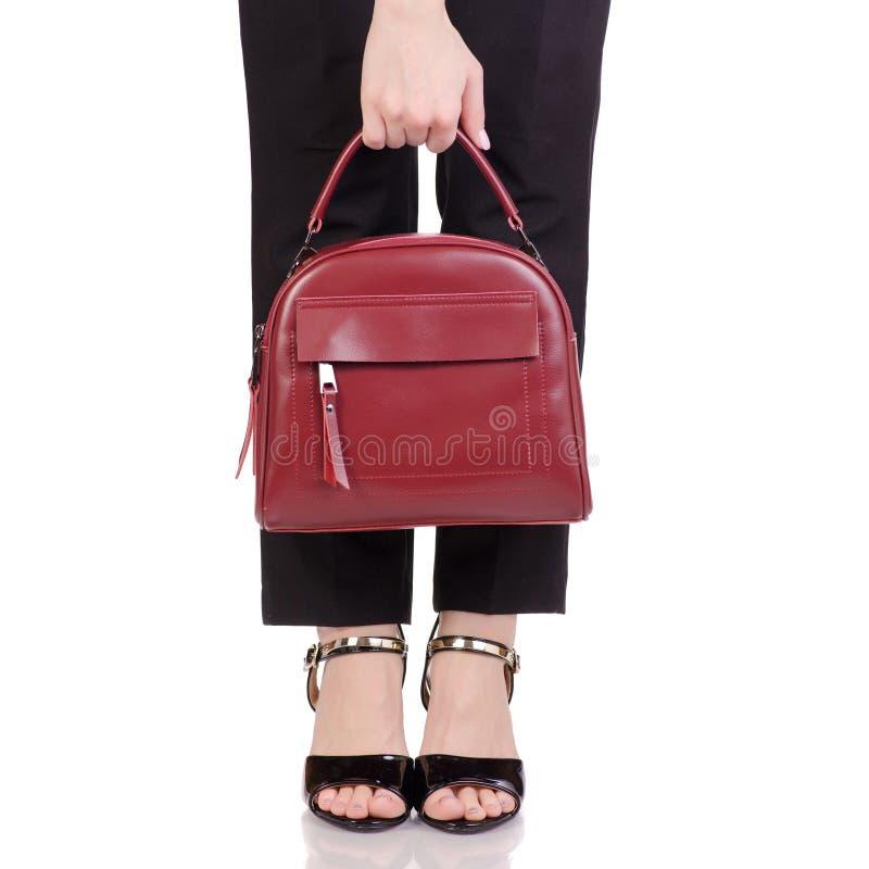 Le gambe femminili nel nero classico ansima le scarpe nere della lacca con la borsa di cuoio rossa a disposizione fotografie stock libere da diritti