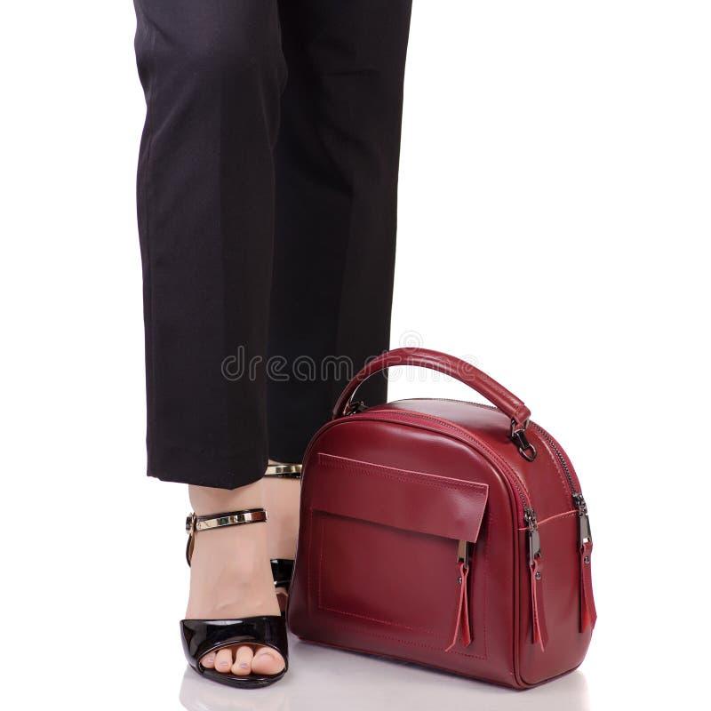 Le gambe femminili nel nero classico ansima le scarpe nere della lacca con la borsa di cuoio rossa a disposizione immagini stock