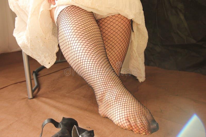 Le gambe femminili nelle calze sono allungate in avanti Fatica e pesantezza alle gambe dopo un giorno di lavoro fotografie stock libere da diritti