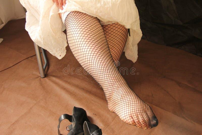 Le gambe femminili nelle calze sono allungate in avanti Fatica e pesantezza alle gambe dopo un giorno di lavoro fotografia stock libera da diritti