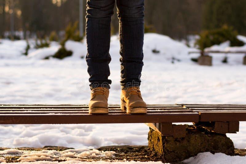 Le gambe femminili stanno stando sul banco nel giorno soleggiato dell'inverno Fondo vago dei raggi di tramonto e della neve Girk  immagini stock