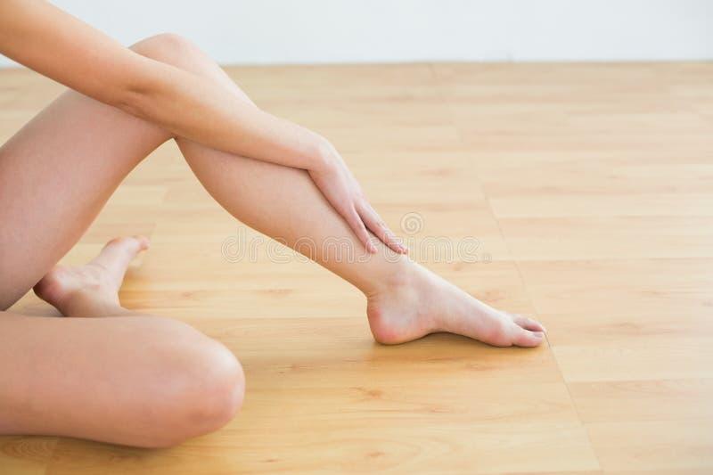 Le gambe tonificate e la mano della donna fotografie stock