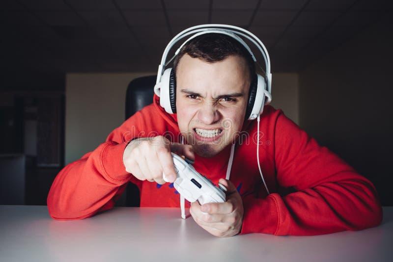 Le gamer émotif joue des matchs à domicile sur la manette Le jeune homme joue des jeux d'ordinateur utilisant un gamepad image libre de droits