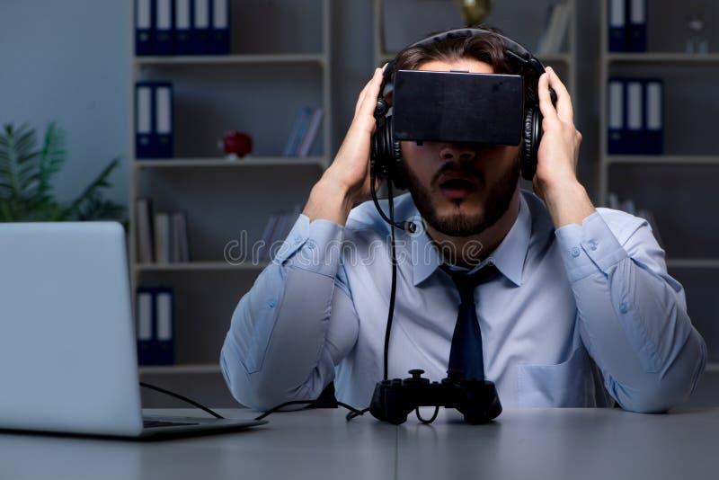 Le gamer d'homme d'affaires restant tard pour jouer des jeux photographie stock