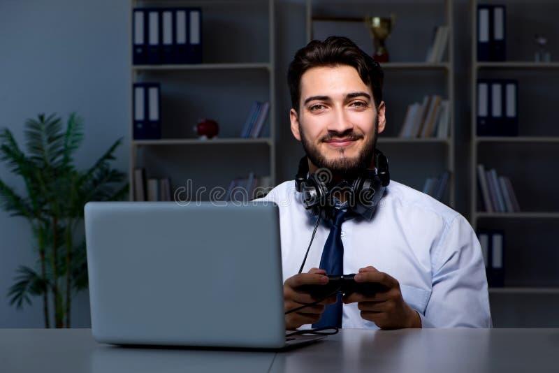 Le gamer d'homme d'affaires restant tard pour jouer des jeux photo stock