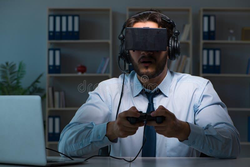 Le gamer d'homme d'affaires restant tard pour jouer des jeux photographie stock libre de droits