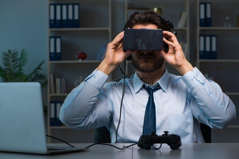 Le gamer d'homme d'affaires restant tard pour jouer des jeux images stock