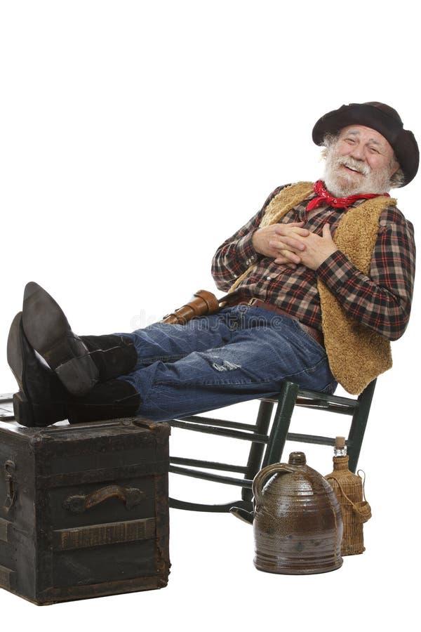Le gammal cowboy i gungstol med fot upp fotografering för bildbyråer