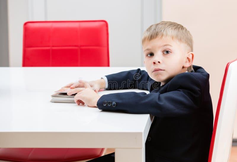 Le garçon à la table avec des photos de plate-forme photographie stock libre de droits