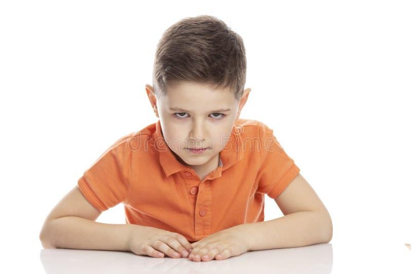 Le garçon écolier sérieux de froncement de sourcils dans un T-shirt orange lumineux de polo s'assied à une table Plan rapproch? I photo stock