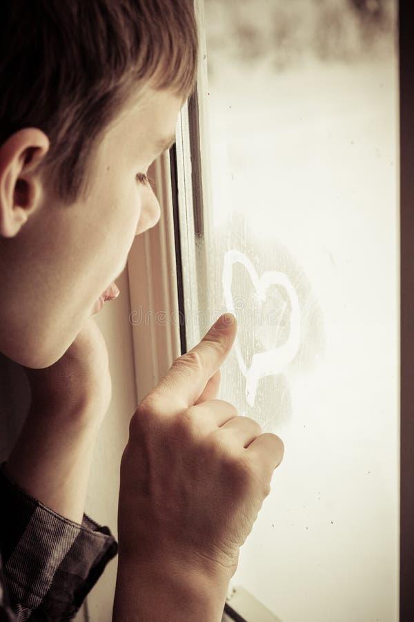 Le garçon écrit un coeur avec le doigt en brume sur la fenêtre images stock