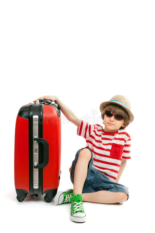 Le garçon élégant s'assied à une valise photos stock