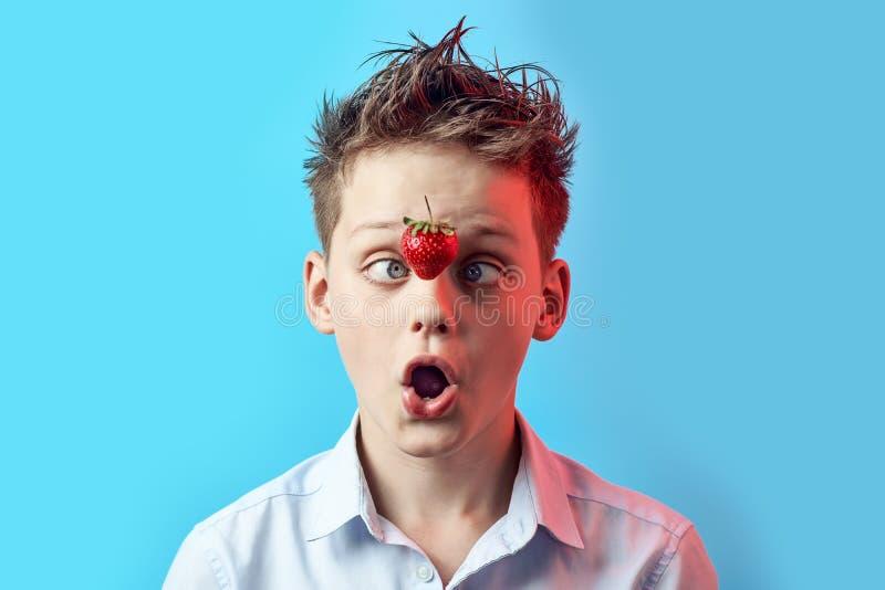 Le garçon étonné avec une fraise en baisse a louché ses yeux à son nez sur un fond bleu photos libres de droits