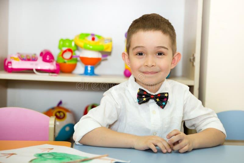 Le garçon adorable d'enfant dessine une brosse et des peintures dans la chambre de crèche Enfant dans le jardin d'enfants en clas image stock
