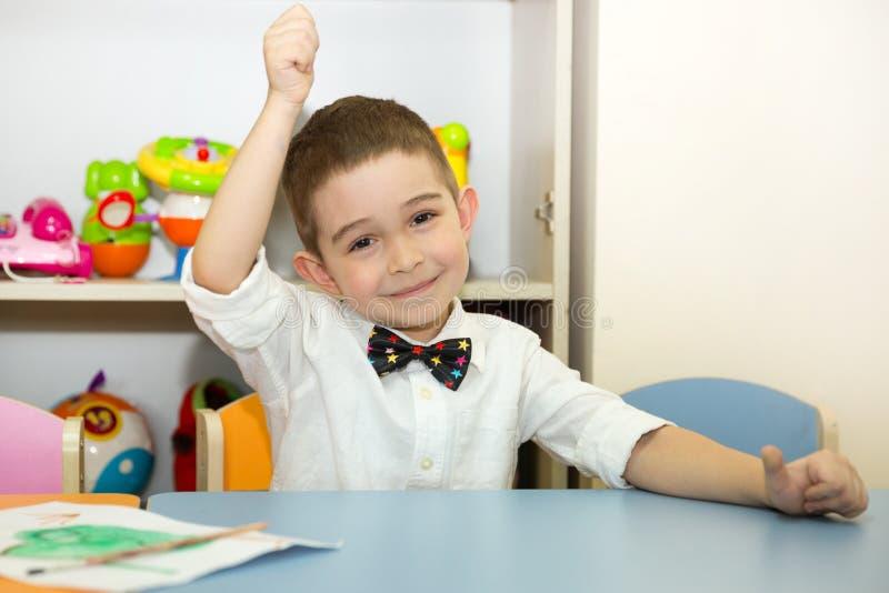 Le garçon adorable d'enfant dessine une brosse et des peintures dans la chambre de crèche Enfant dans le jardin d'enfants en clas images libres de droits