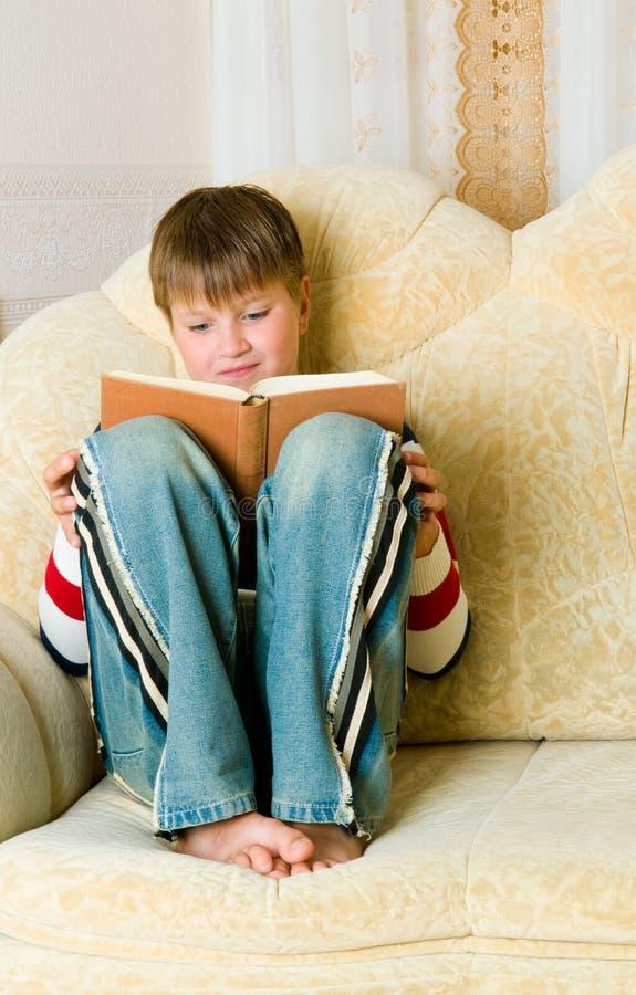 Le garçon affiche le livre photographie stock