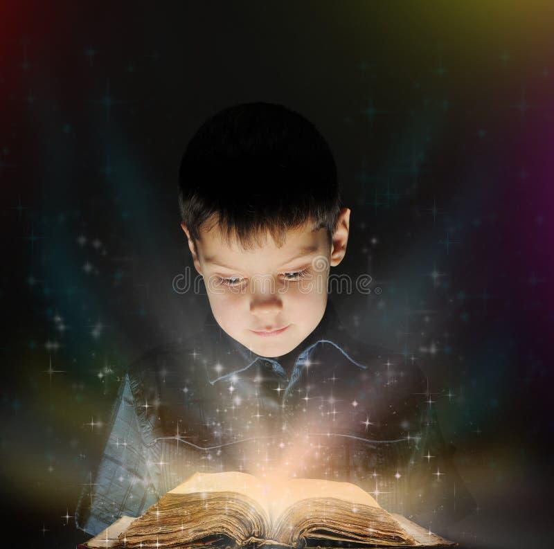 Le garçon affiche un livre magique image libre de droits