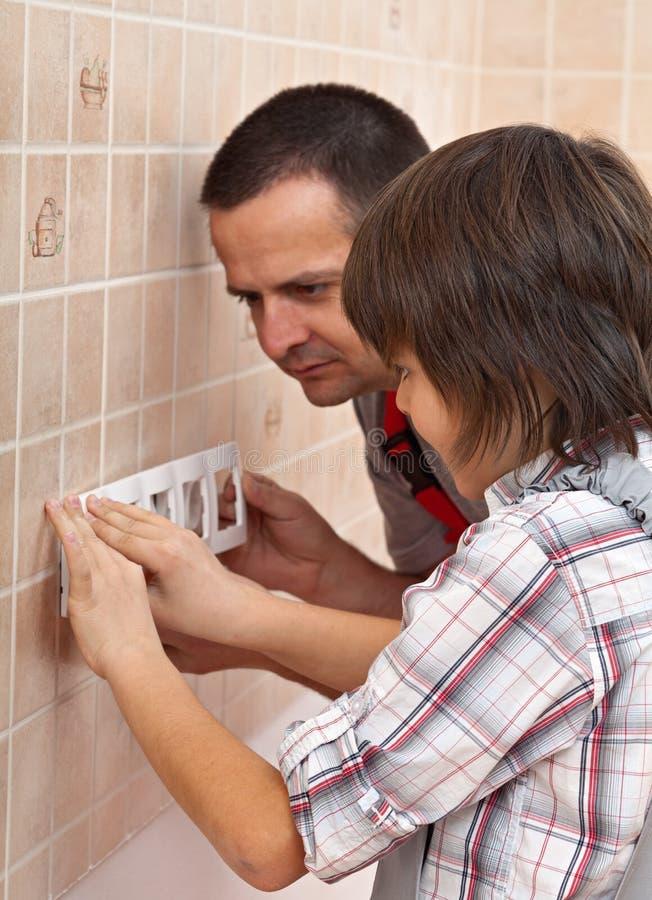 Le garçon aidant son père installent le panneau avant de wal électrique photographie stock