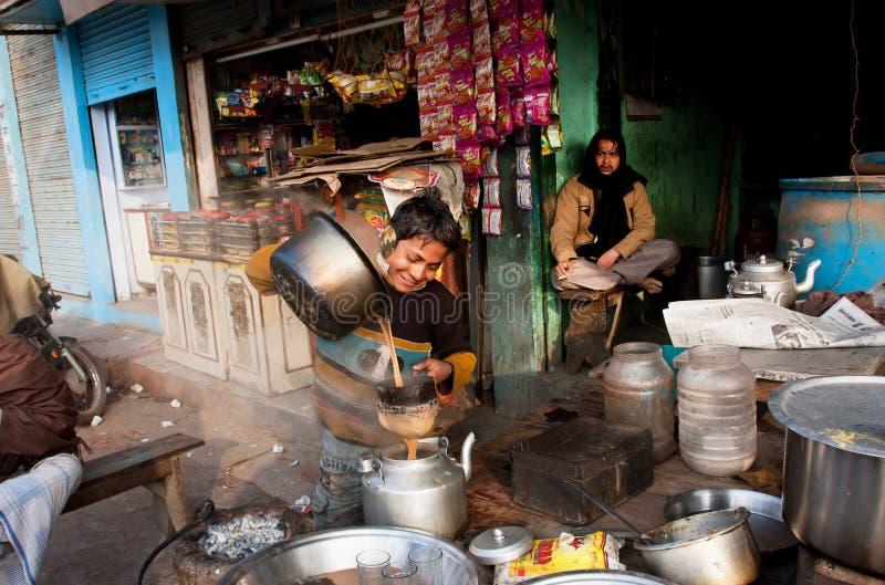Le garçon aide à faire cuire le masala indien de thé avec du lait et des épices images libres de droits