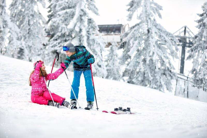 Le garçon aide à la fille à se lever de la neige avec des skis image stock