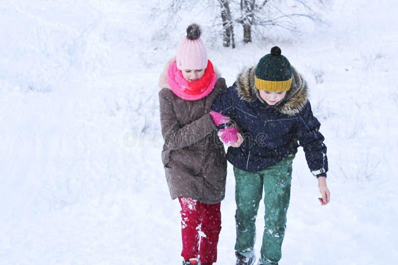 Le garçon aide la fille à s'élever hors de la neige et à passer images stock