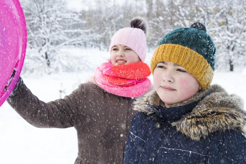 Le garçon aide la fille à s'élever hors de la neige et à se déplacer image libre de droits