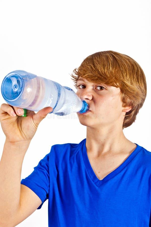 Le garçon altéré est eau potable image stock