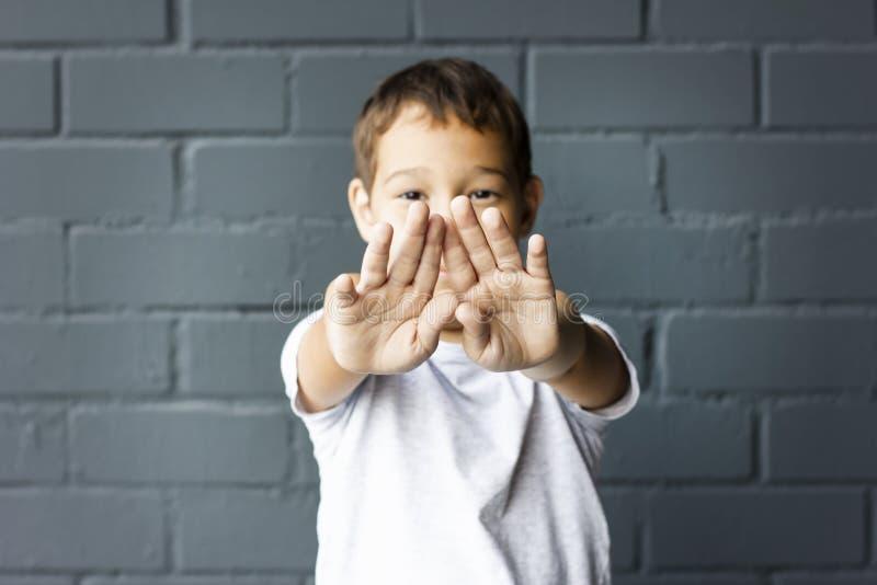 Le garçon 8 années a étiré ses mains en avant, font des gestes non sur le mur gris photos stock
