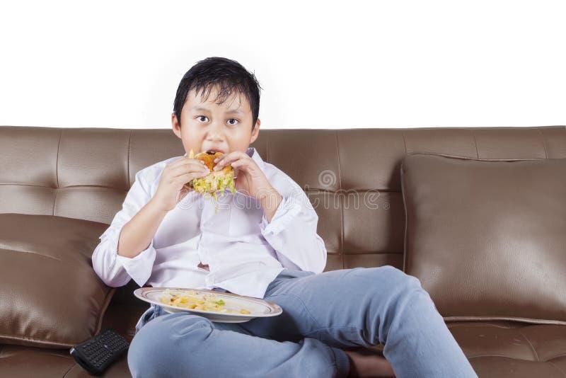 Le garçon apprécient le cheeseburger tout en regardant la TV photo stock