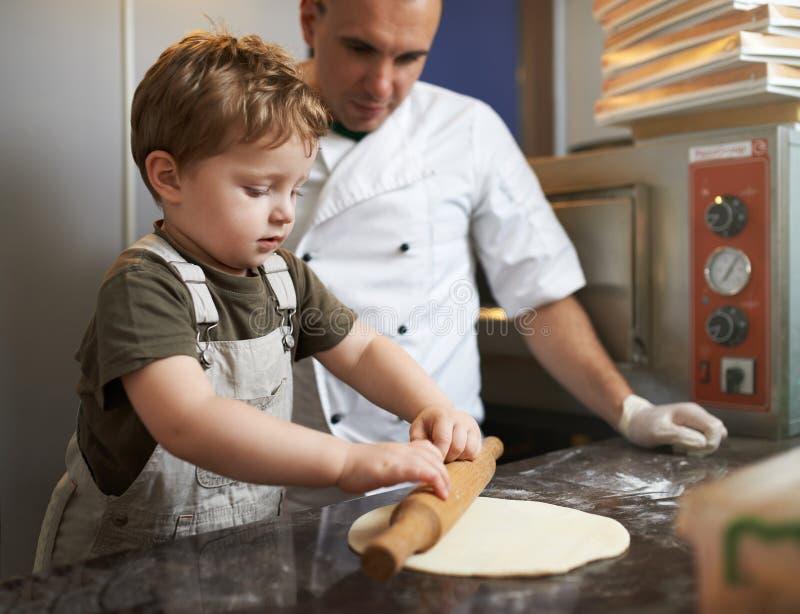 Le garçon apprend à dérouler la pâte de pizza image libre de droits