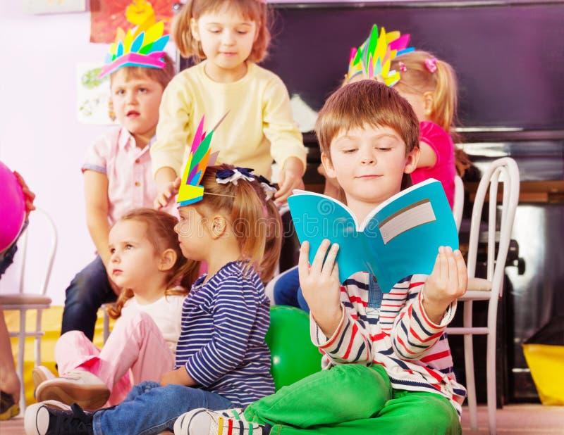 Le garçon apprend à lire dedans la classe de jardin d'enfants photo libre de droits