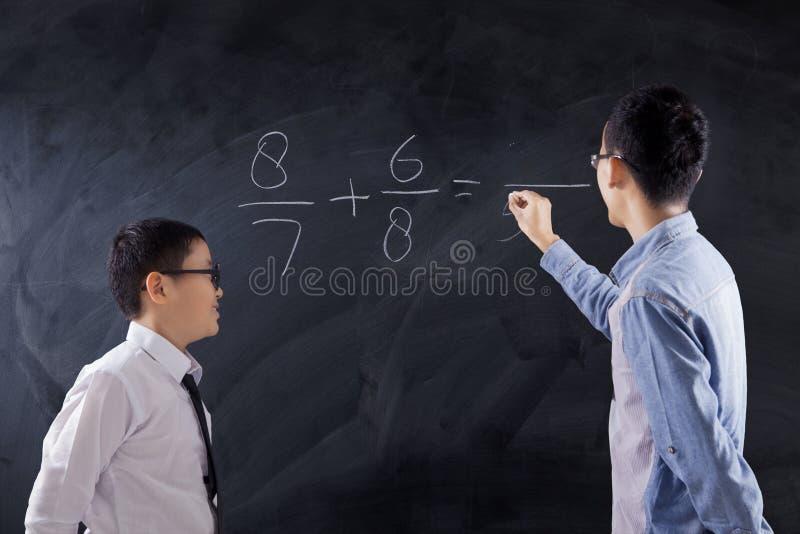Le garçon apprend la leçon de maths dans la classe photos stock