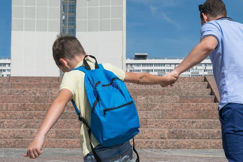 Le garçon après les vacances ne veut pas étudier et aller à l'école, résiste à ses parents image libre de droits