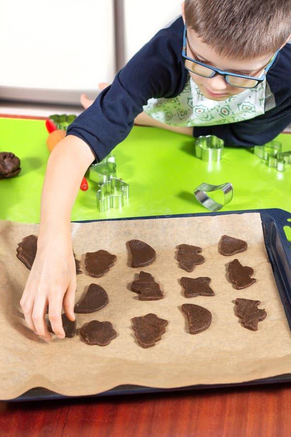 Le garçon arrange des formes coupées de biscuit sur un plateau de cuisson À l'arrière-plan, cuttersB de table basse de silicone e photos stock