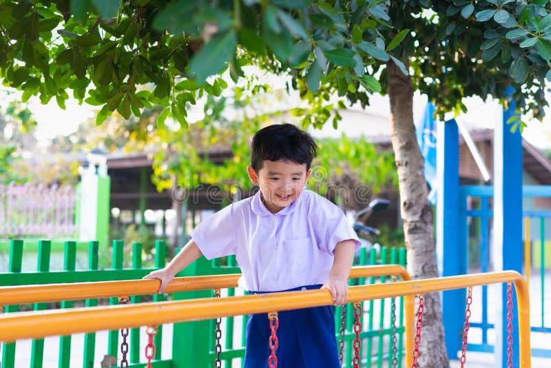 Le garçon asiatique accrochent la barre de singe ou la barre d'équilibre pour l'équilibre au terrain de jeu extérieur image libre de droits