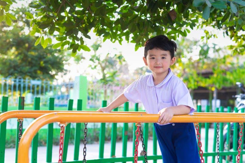 Le garçon asiatique accrochent la barre de singe ou la barre d'équilibre pour l'équilibre au terrain de jeu extérieur photographie stock libre de droits