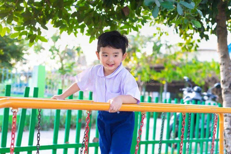 Le garçon asiatique accrochent la barre de singe ou la barre d'équilibre pour l'équilibre au terrain de jeu extérieur images stock