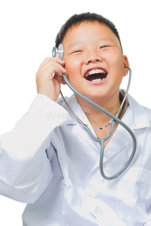 Le garçon asiatique heureux joue un docteur photographie stock libre de droits