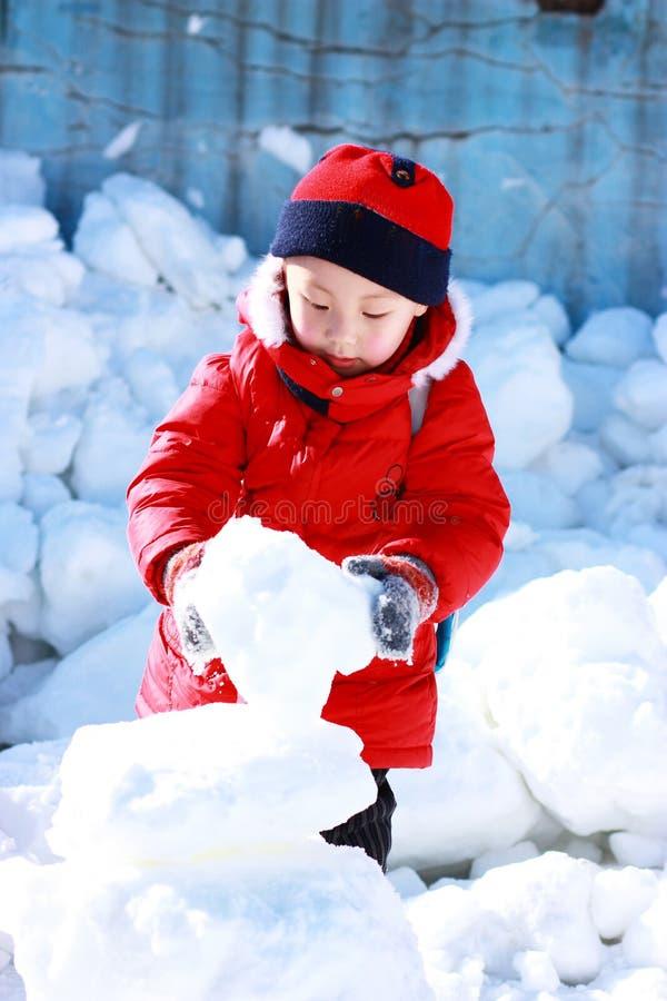 Le garçon asiatique joue la neige photos libres de droits