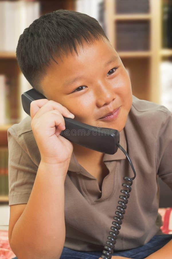 Le garçon asiatique semble heureux au téléphone photos stock