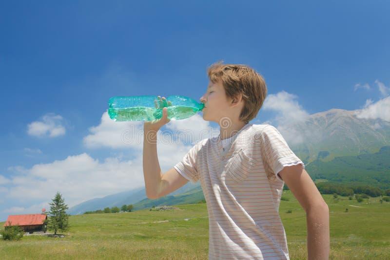 Le garçon assoiffé buvant l'eau claire de la bataille dans le sien remet la haute dans les Alpes photos stock