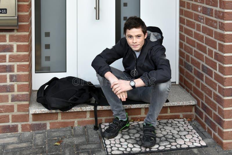 Le garçon attend quelqu'un avec la clé d'entrée principale photo libre de droits
