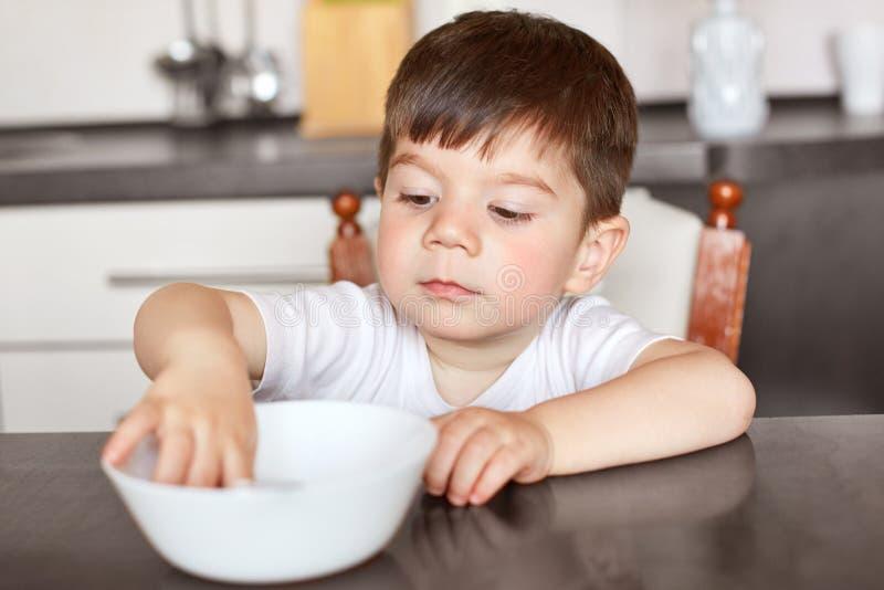 Le garçon attirant avec l'aspect agréable, s'assied à la table de cuisine, regarde dans la cuvette blanche, attend le dîner, ayan images stock