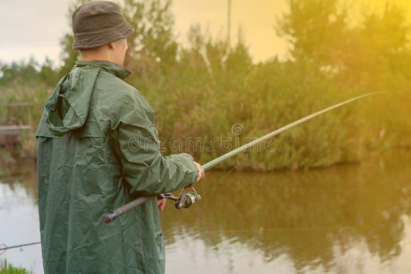Le garçon attrape un filet par le lac photo stock