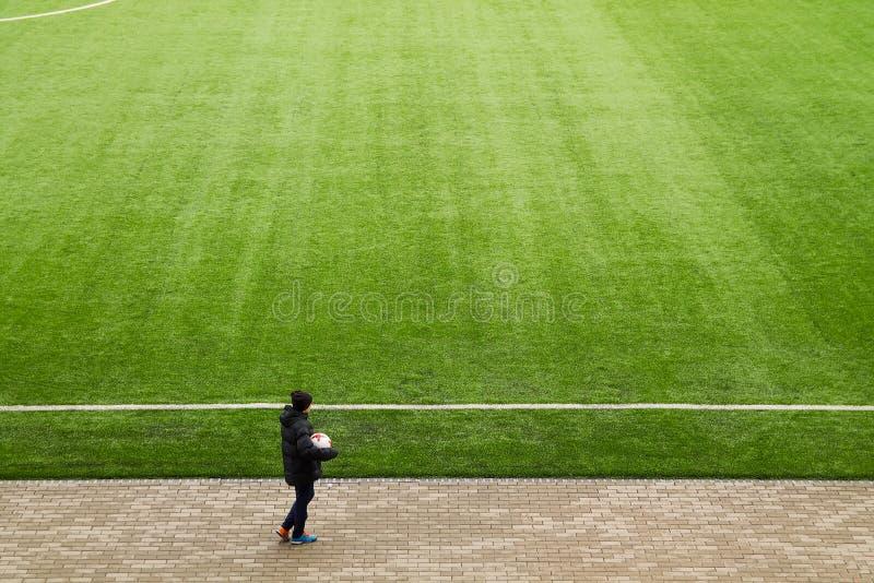 Le garçon au bord d'un terrain de football photos stock