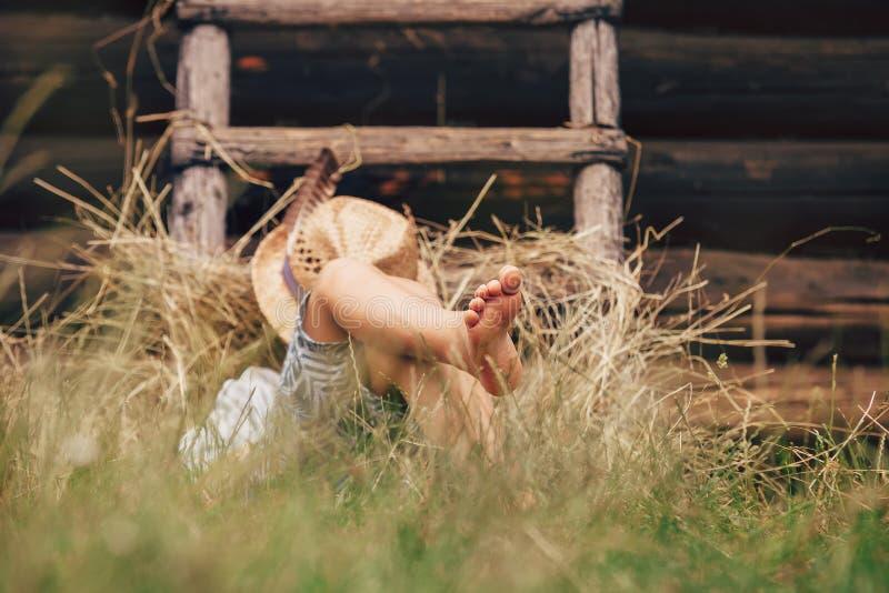 Le garçon aux pieds nus dort sur l'herbe près de l'échelle dans la meule de foin images stock